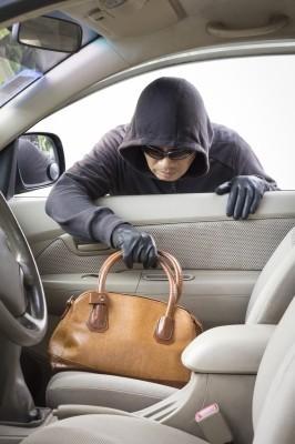 Imagem de um ladrão arrebatando uma bolsa através da janela de veículo, ocasionando a perda de documentos