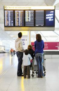 Imagem de família no saguão de aeroporto observando horários de embarque no letreiro eletrônico