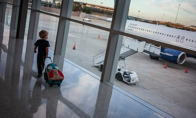 Criança no aeroporto carregando sua mala e olhando um avião através da janela panorâmica