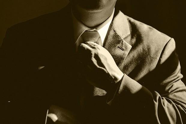 Como se vestir na entrevista de emprego - homem de terno ajustando a gravata