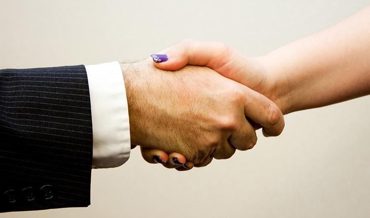 Aperto de mão em close entre homem e mulher após uma entrevista de emprego bem sucedida