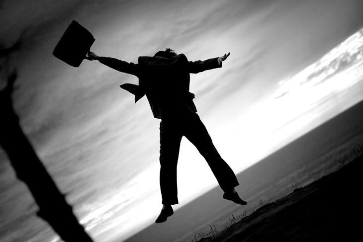 Homem vestido com terno e carregando uma maleta pulando de alegria ao conquistar o primeiro emprego