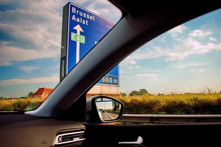 Passageiro no interior de carro trafegando olhando o espelho retrovisor. Família em férias amparada por seguro viagem europa